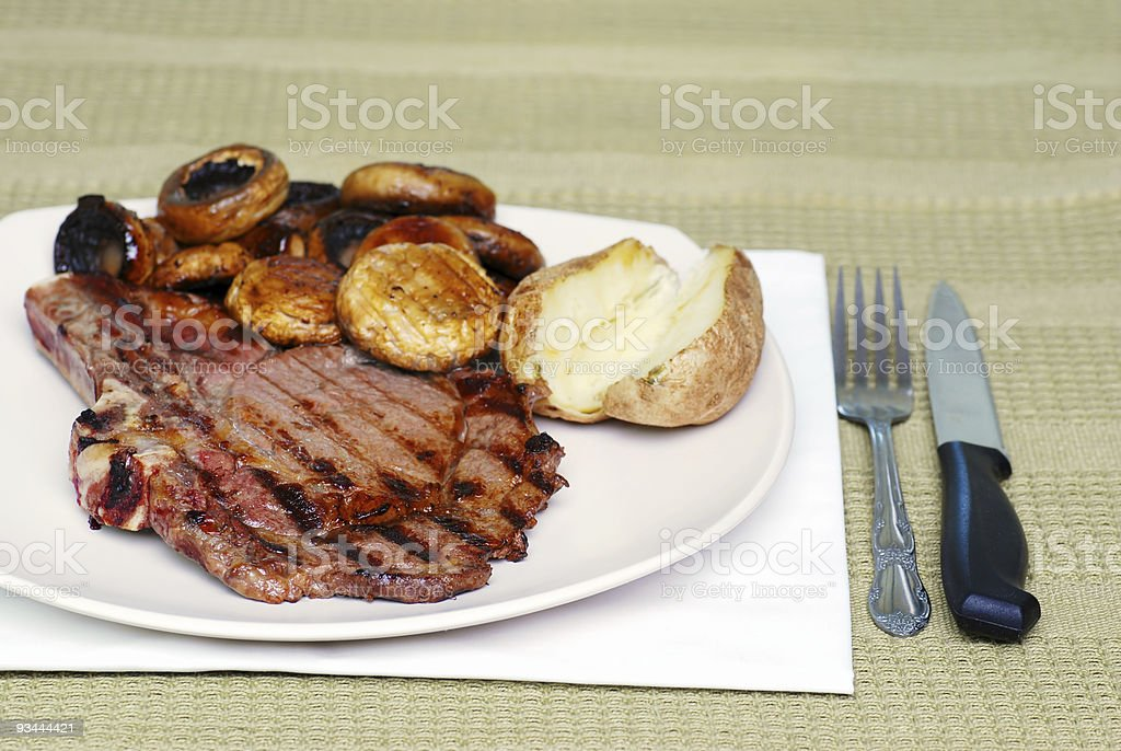 Rib steak with mushrooms and baked potato royalty-free stock photo
