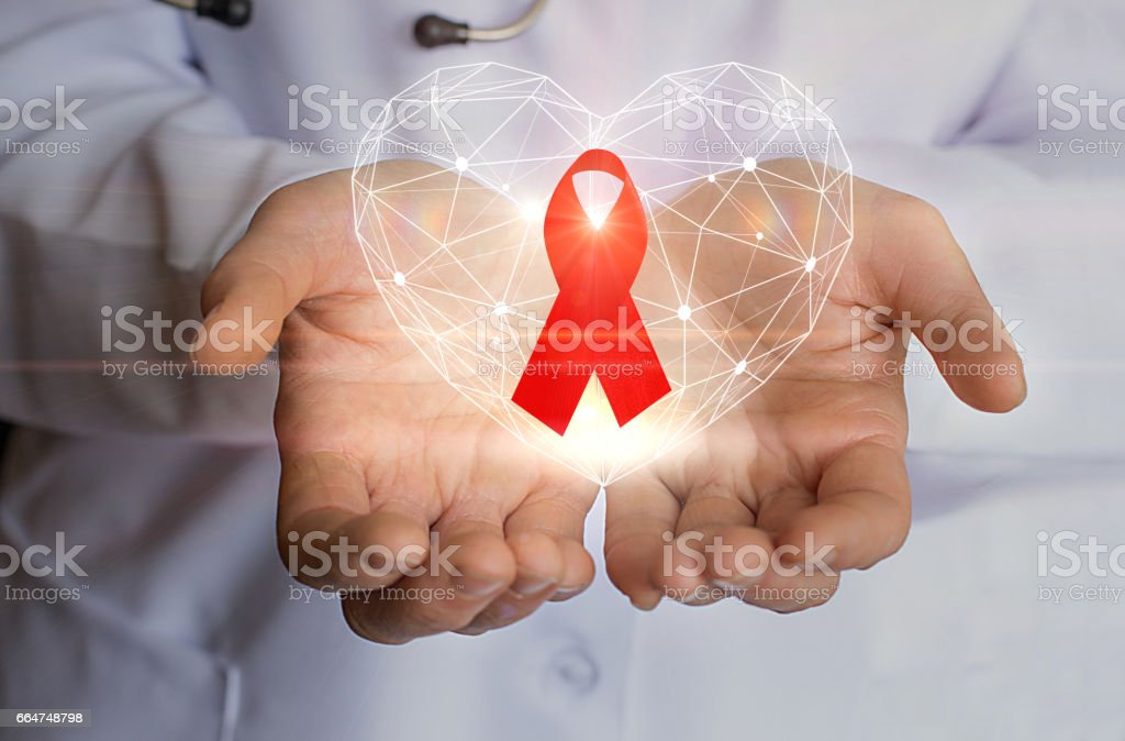Ribbon for the fight against AIDS and heart symbol in the hands. stock photo