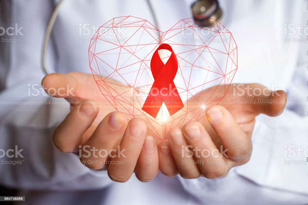 Ribbon for the fight against AIDS in the hands. stock photo