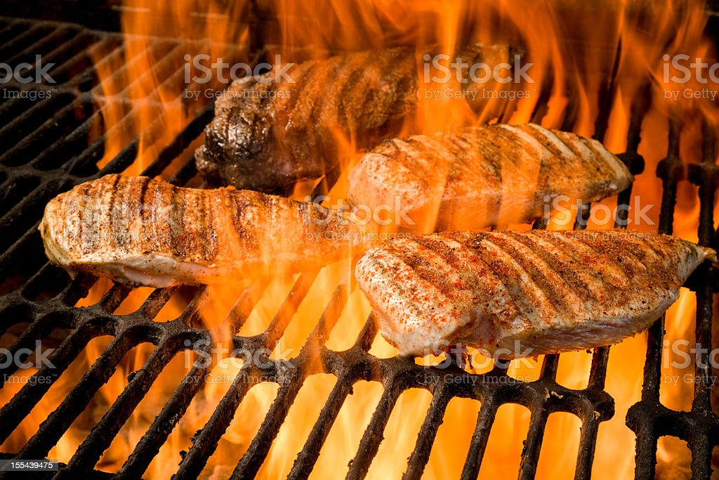 Ribeye Steak and Chicken Breasts on Grill with Fire royalty-free stock photo