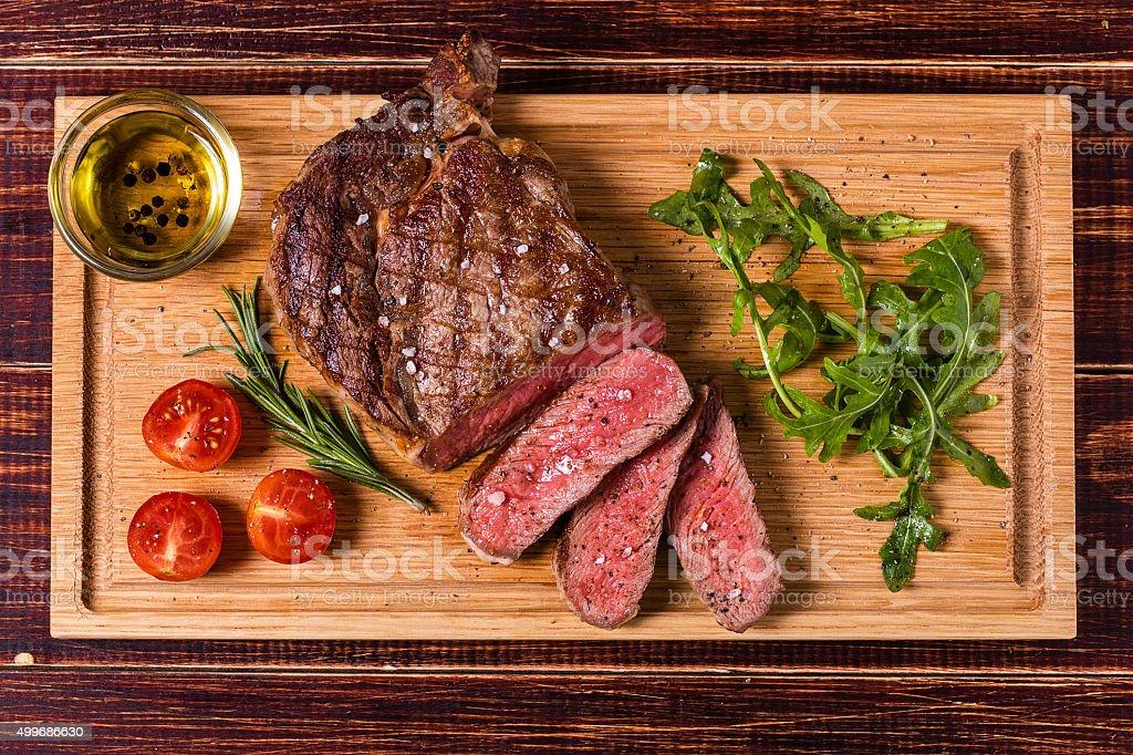 Ribeye steak with arugula and tomatoes. stock photo