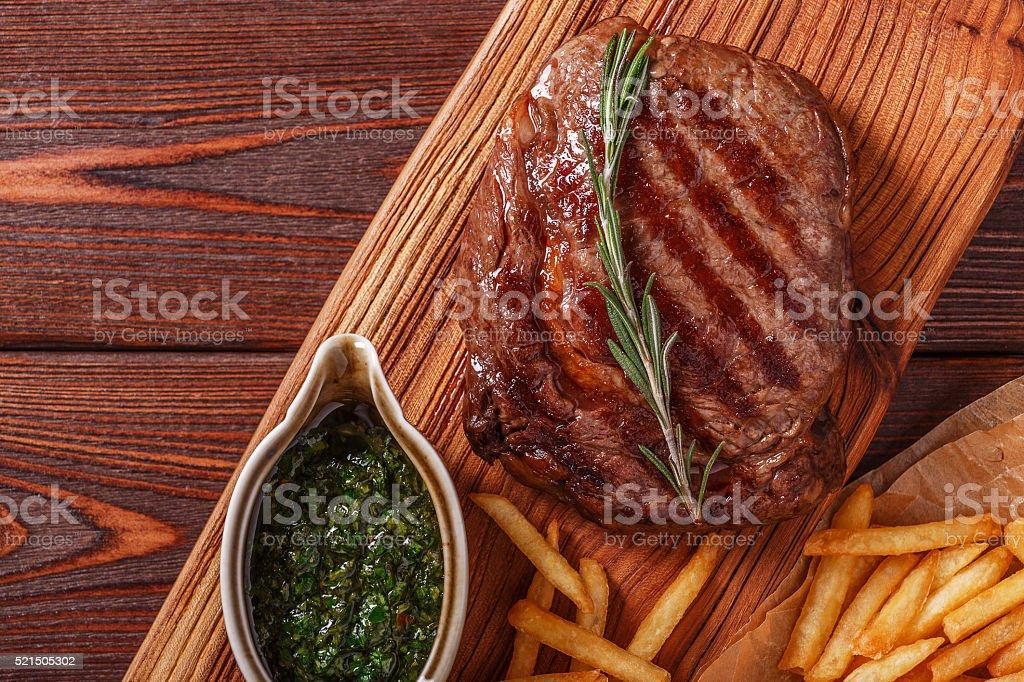 Ribeye steak with chimichurri sauce and french fries. stock photo