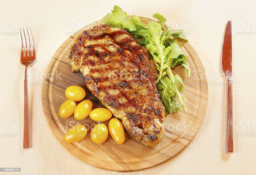 Ribeye steak with fresh greenery and tomatoes royalty-free stock photo