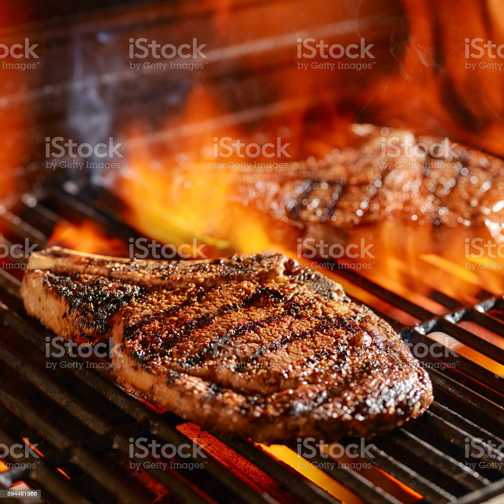 ribeye steaks on the grill over the open flame stock photo