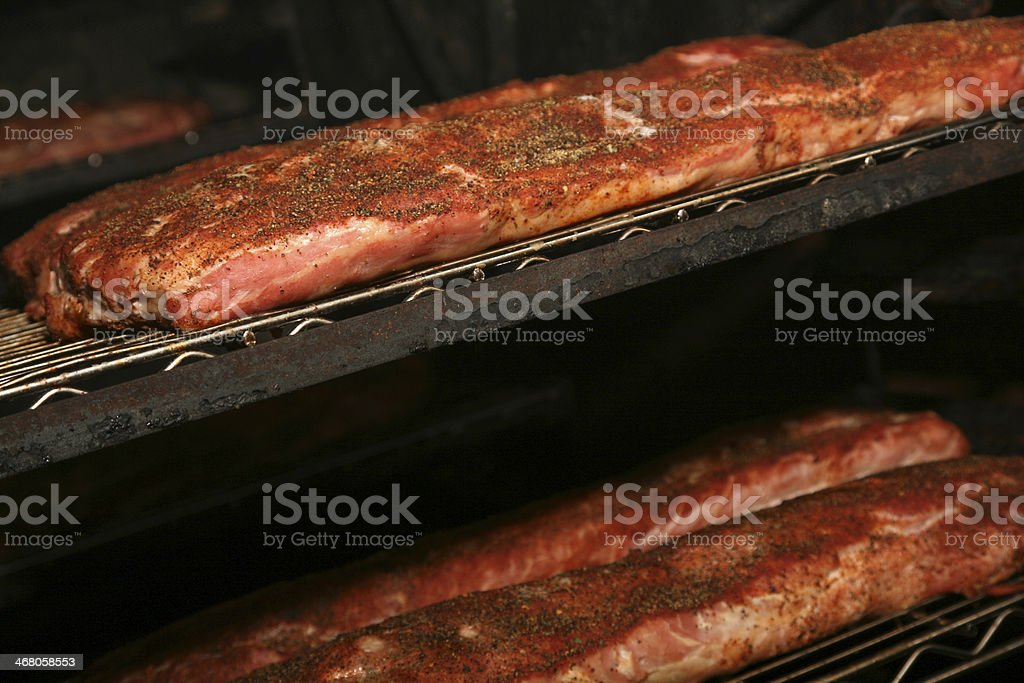 BBQ ribs cooking in smoker stock photo