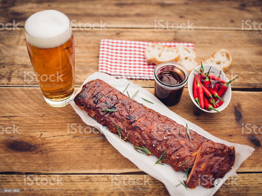 Ribs with sauce, chillies and a tall glass of beer stock photo