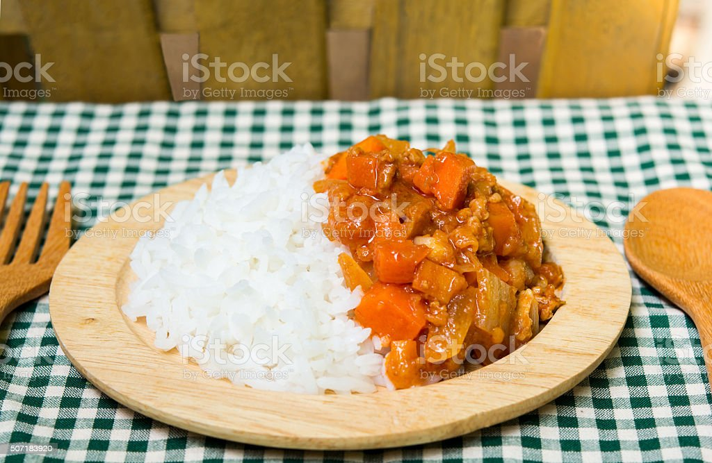 rice and spicy curry on wood plate stock photo