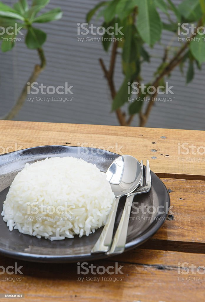 rice and spoon on black dish royalty-free stock photo