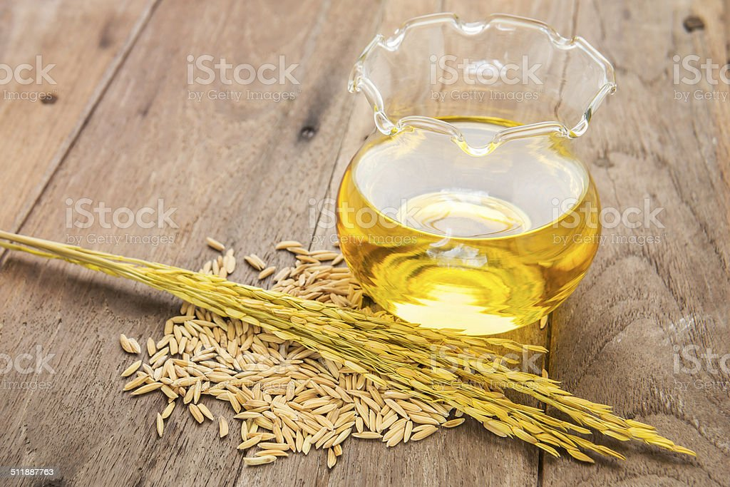 Rice bran oil in bottle glass and unmilled rice stock photo