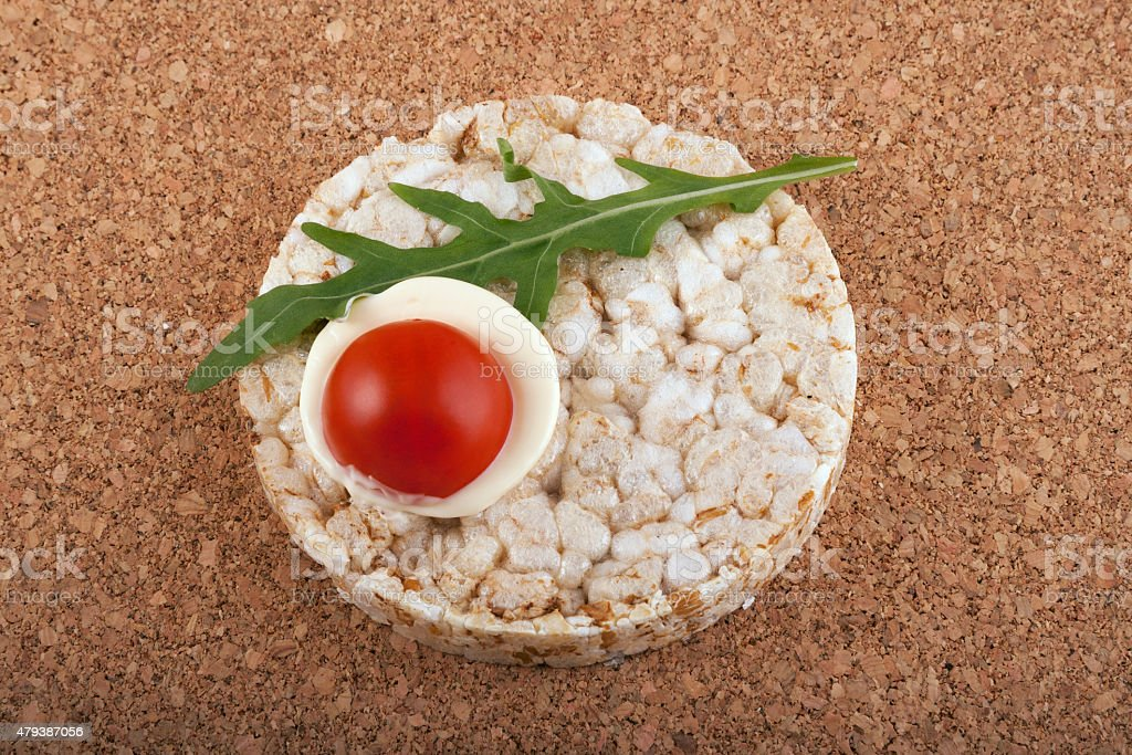 Rice cracker with tomato on a cork table stock photo