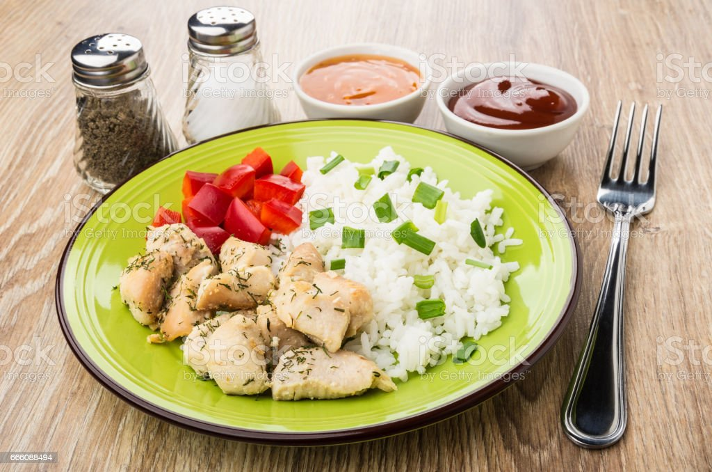 Rice, fried chicken meat and sweet pepper, spices, sauces stock photo
