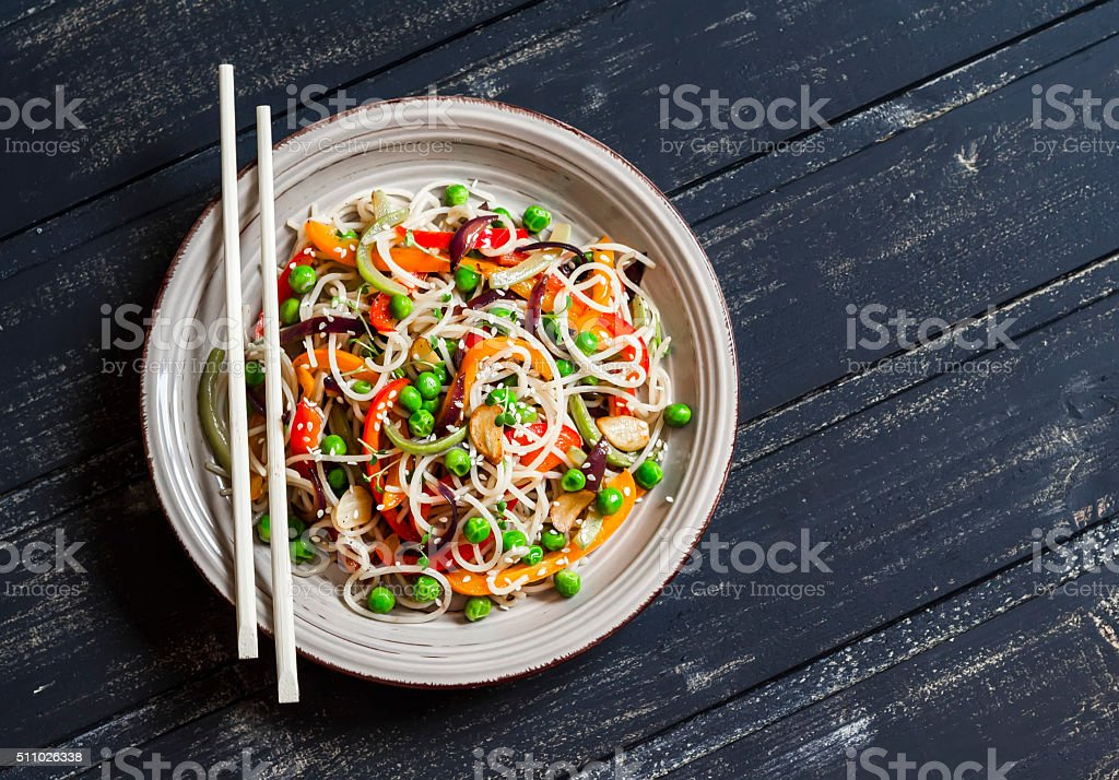 Rice noodles with vegetable stir fry on  wooden background stock photo