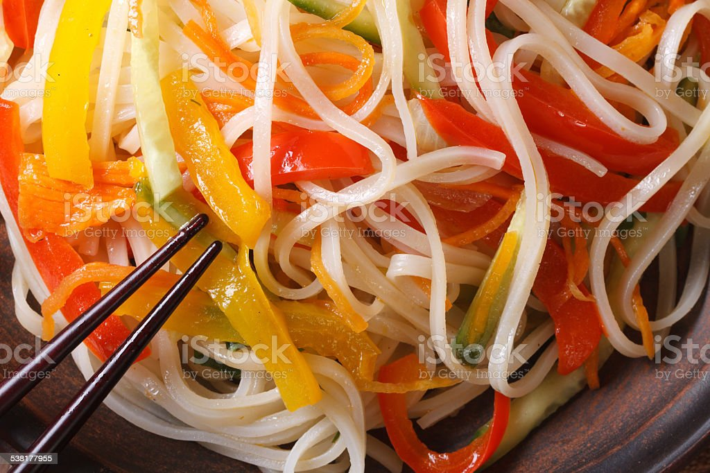 Rice noodles with vegetables macro on a plate. horizontal top stock photo
