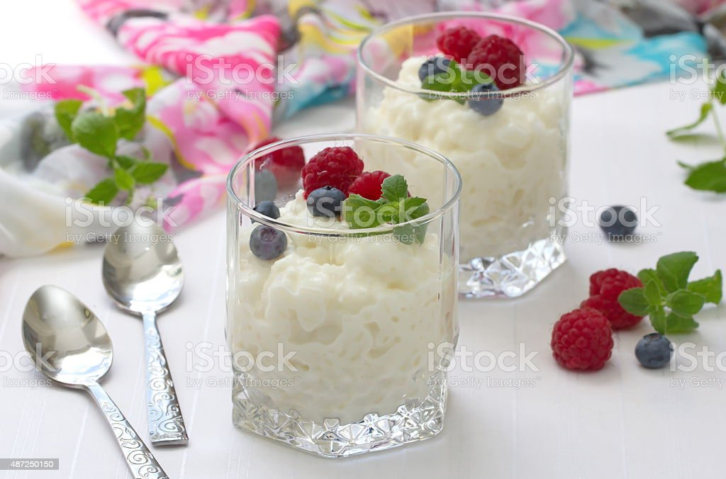 Rice pudding with berries in glasses stock photo