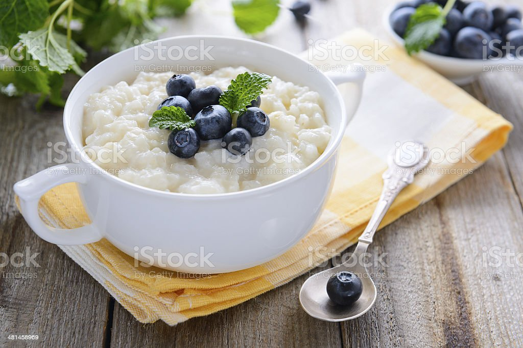 Rice pudding with bilberry in white bowl stock photo