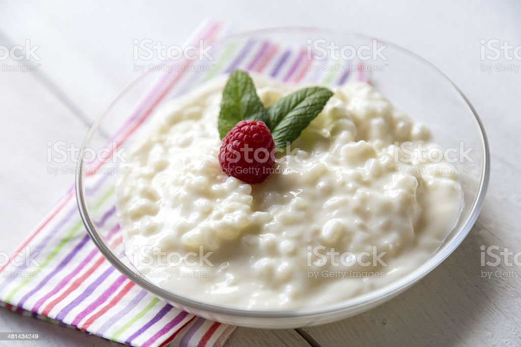 Rice pudding with mint and raspberry stock photo