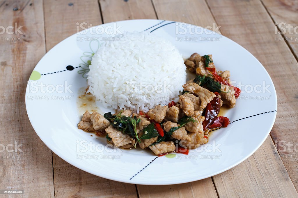 Rice topped with stir-fried pork and basil stock photo