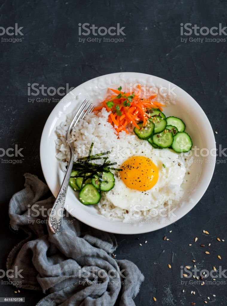 Rice with fried egg, pickled carrots, cucumber and seaweed. Healthy diet food concept. Top view, on a dark background stock photo