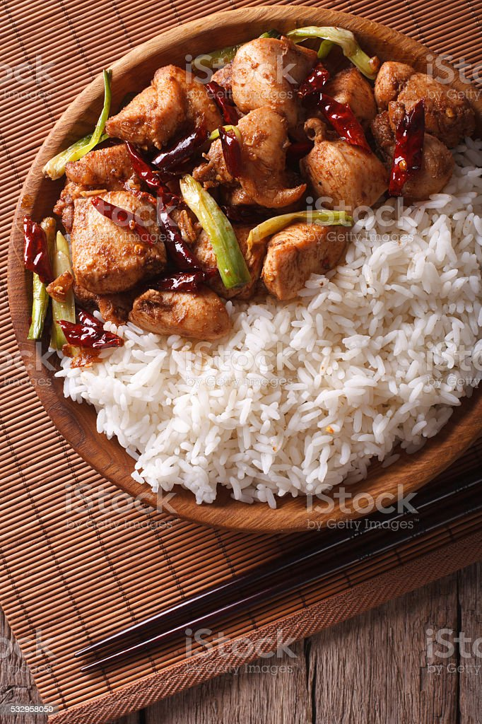 Rice with spicy kung pao chicken close-up. Vertical top view stock photo