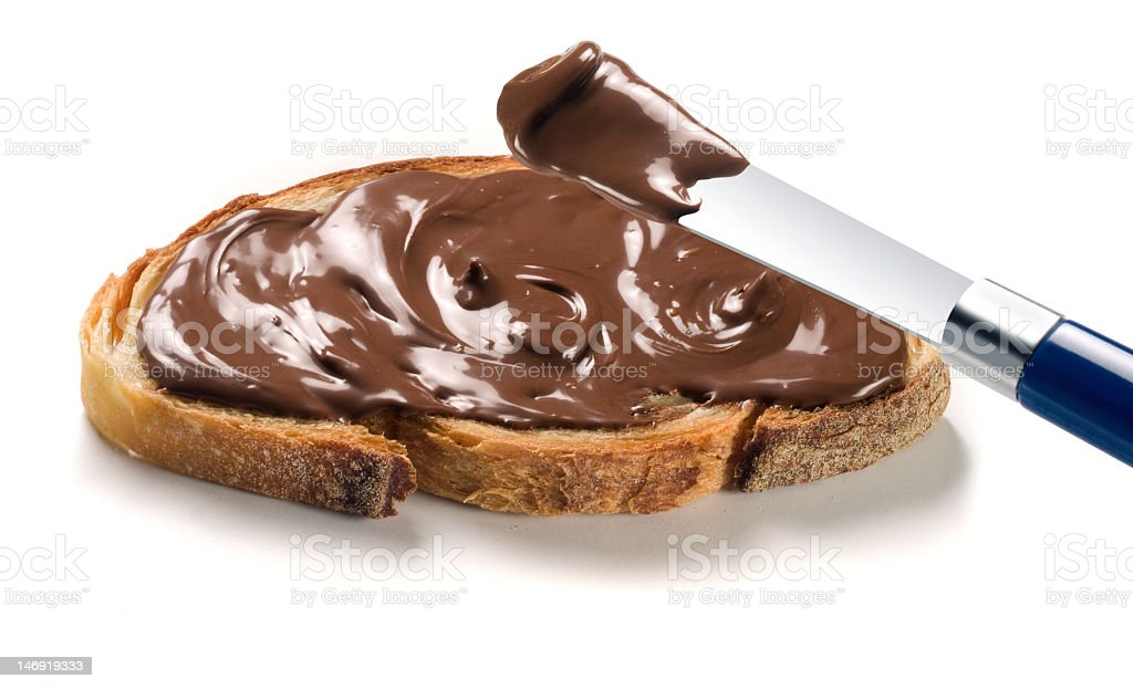 Rich, chocolate cream spread generously on a piece of bread royalty-free stock photo