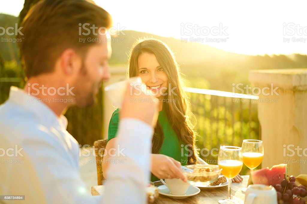 rich couple enjoying breakfast outside with sunshine stock photo