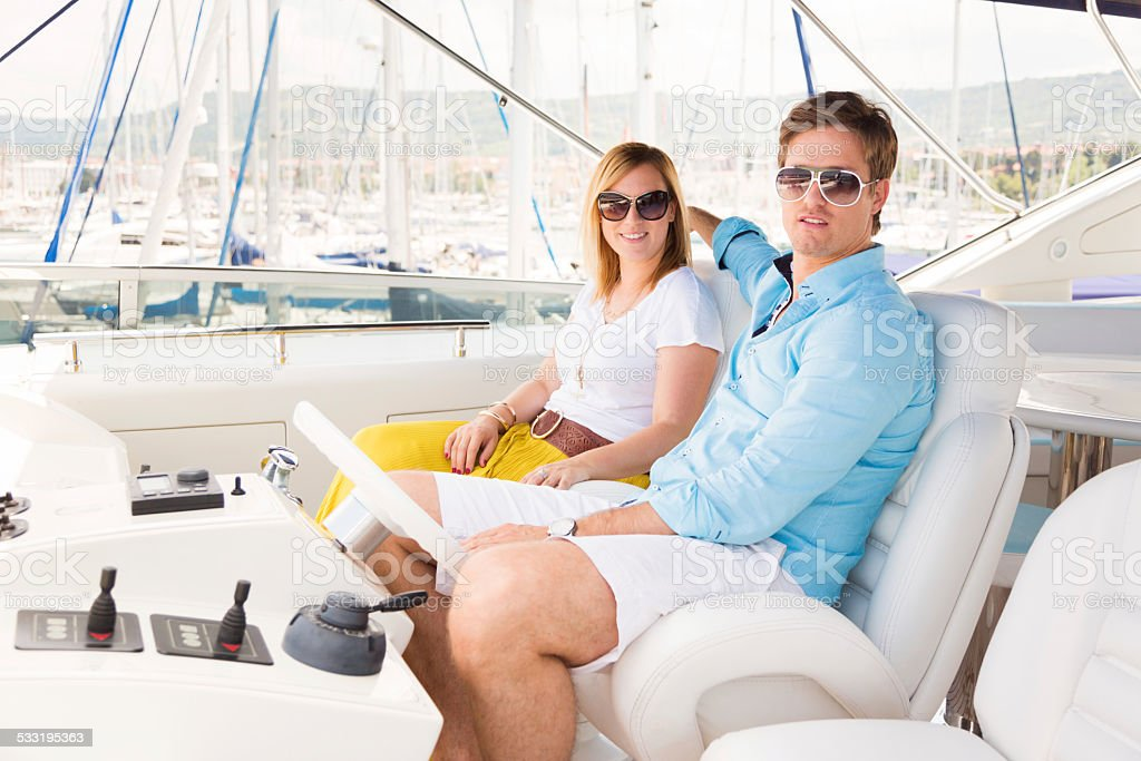 rich couple navigating their yacht out of port stock photo