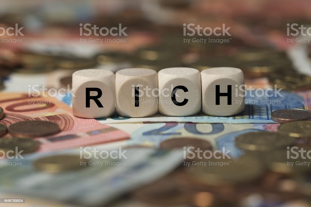 rich - cube with letters, money sector terms - sign with wooden cubes stock photo