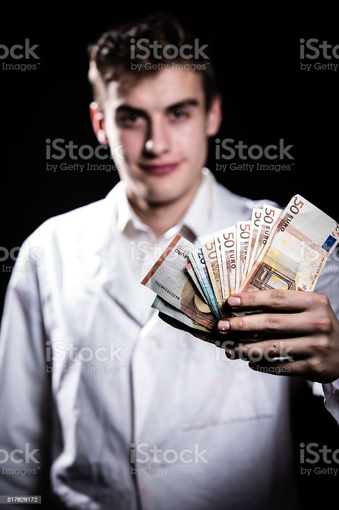 Rich doctor holding money.Corruption and criminal in Health Industry.Recieving bribe stock photo