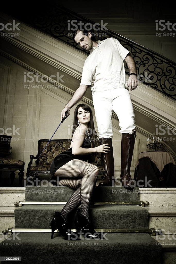Rich Man Hitting Woman With Polo Whip stock photo