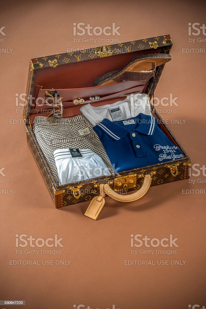 Rich man's vacation suitcase on brown backdrop stock photo