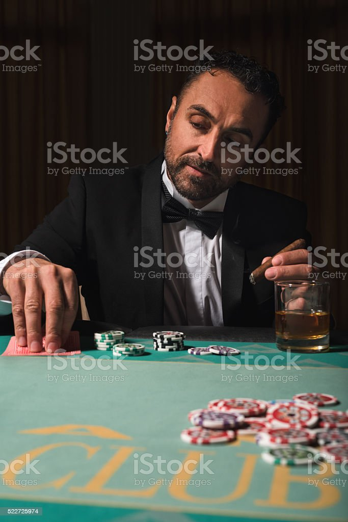 Rich mature man playing poker in a casino stock photo