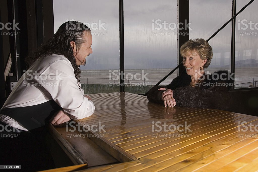 Rich senior woman flirting with a bartender at the bar stock photo