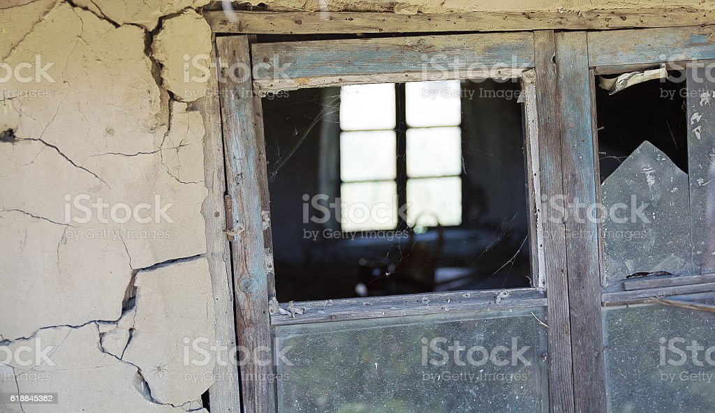 Rickety old wooden window frame with broken window pane. stock photo
