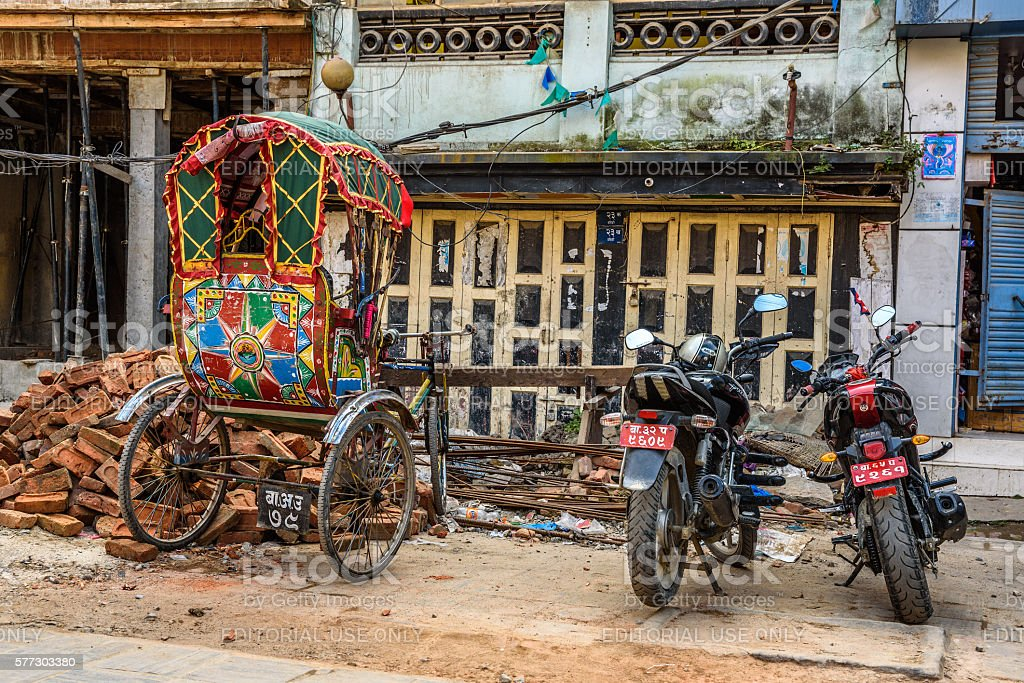 Rickshaw and motorcycles parked in front of damaged houses stock photo