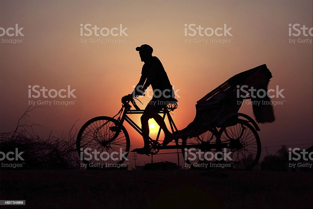 Rickshaw driver riding on the sunset. stock photo