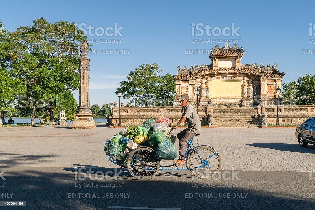 Rickshaw driver transports vegetables on his vehicle stock photo