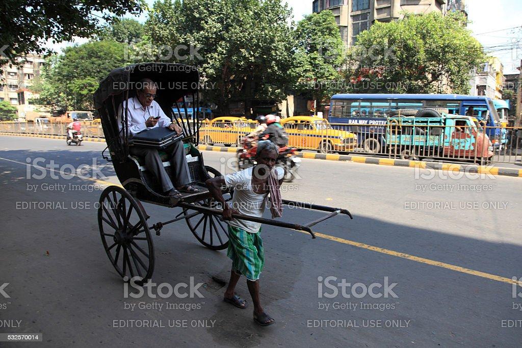Rickshaw man pulls a customer stock photo