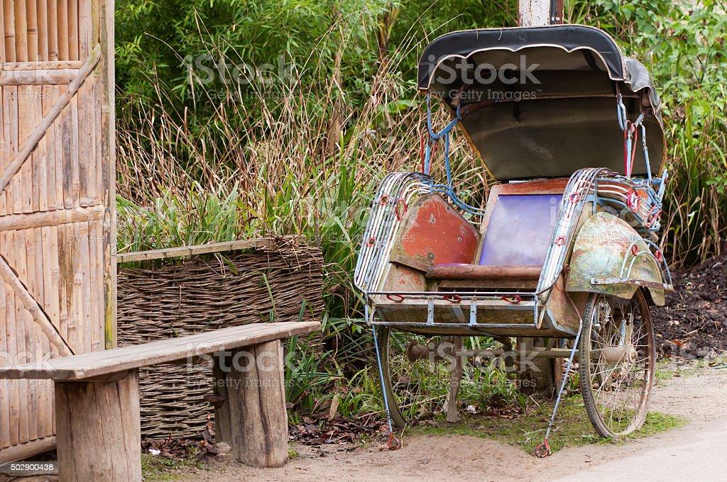 Rickshaw next to a bench stock photo