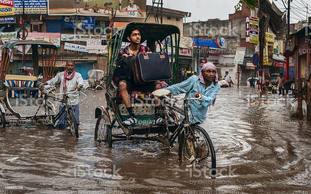 Rickshaws pulling passenger during flash flood, Varanasi, India. stock photo