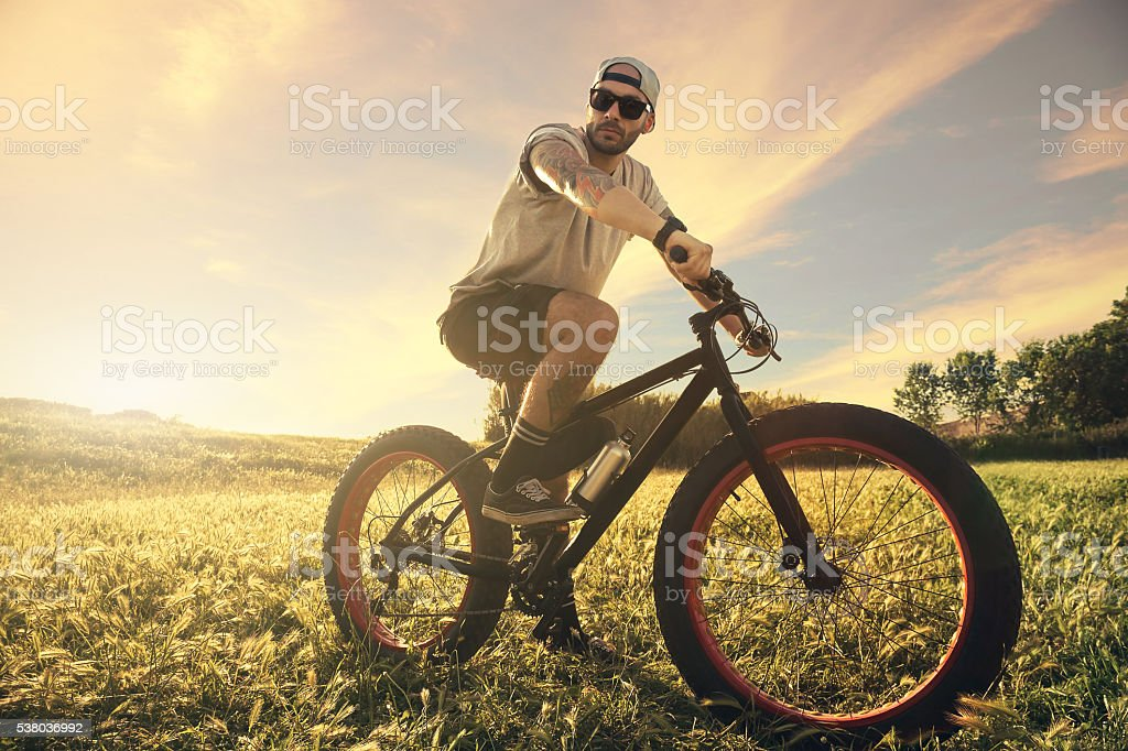 Rider cyclist with bike on sunset stock photo