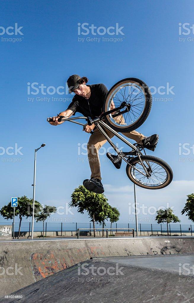 BMX rider jumping in urban environment stock photo