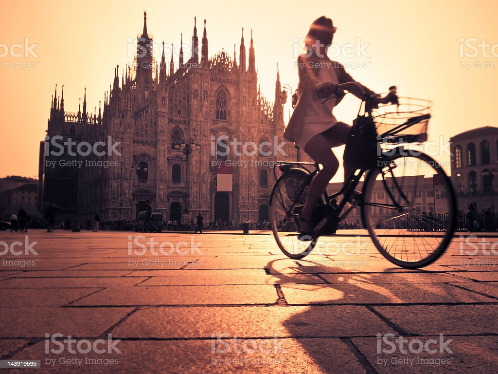 Riding A Bicycle In Milan City At Sunset stock photo