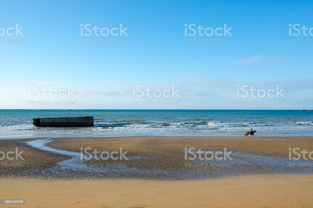 Riding a horse on D-Day beach in Arromanches, Normandy, France stock photo