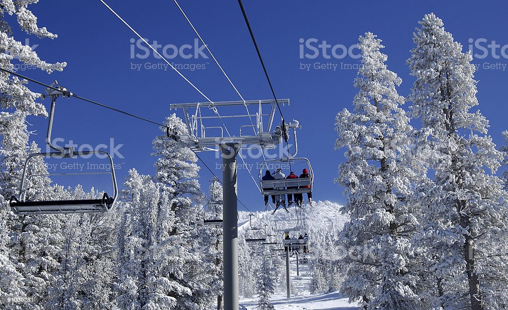 Riding a lift at ski resort. stock photo
