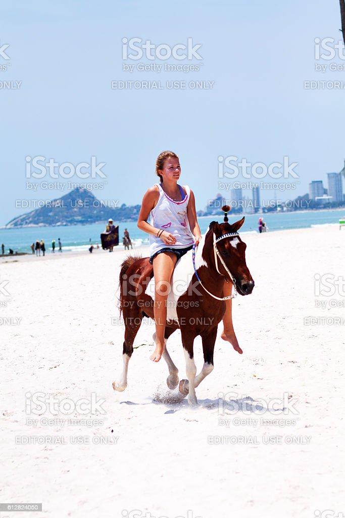 Riding female tourist on beach in Hua Hin stock photo