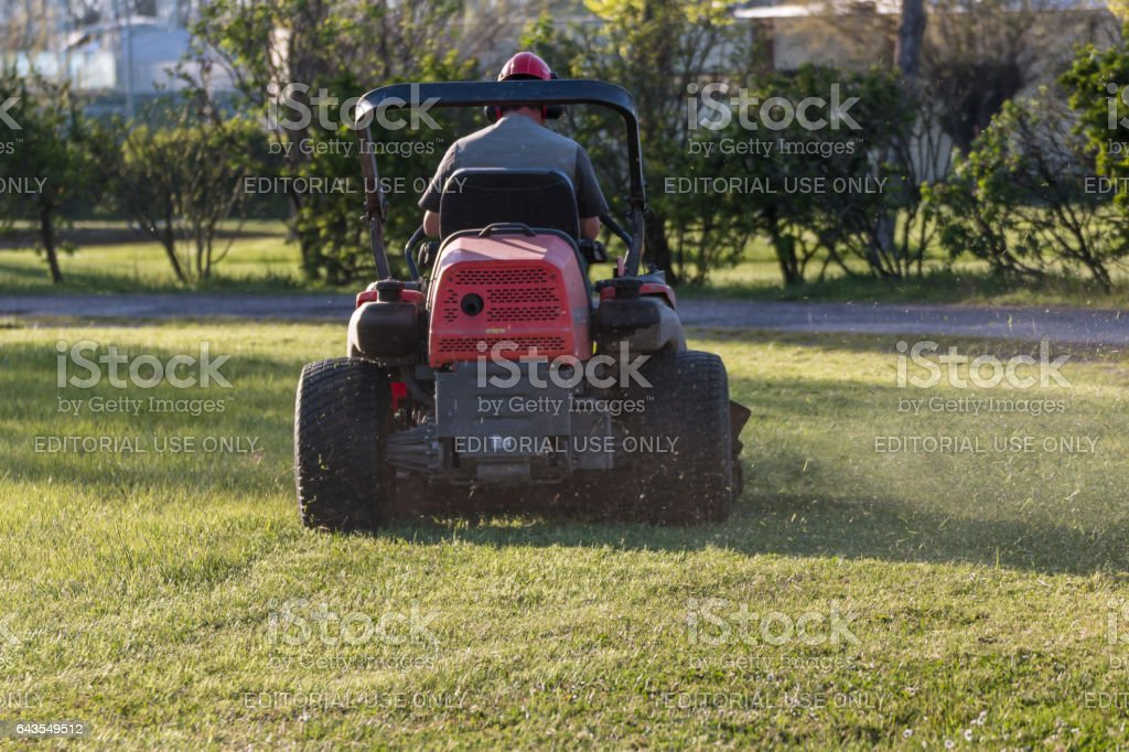 Parma, Italy - june 2015: Riding Lawn Equipment with operator for periodically garden upkeep stock photo