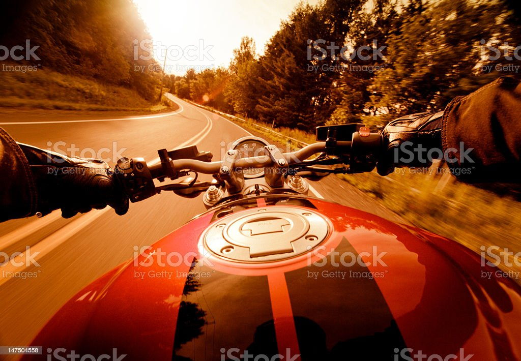 Riding motorcycle in the sunset stock photo
