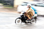 Riding Scooter Through the Rain and Floods with Motion Blur
