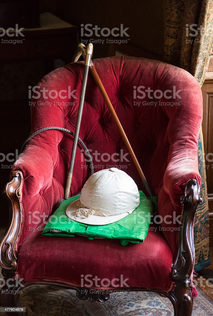 Riding silks and hat on red velvet chair stock photo