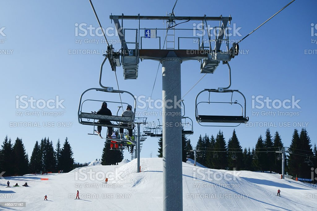 Riding to the ski slopes on the chair lift. stock photo